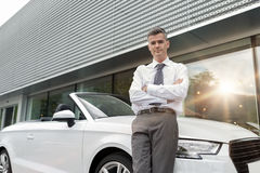 Car salesman posing at the showroom. Confident car salesman leaning on a luxury convertible car, showroom on the background, dealership and business concept stock photography