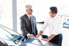 Car salesman sale. Senior car salesman just made a sale to young customer royalty free stock photo