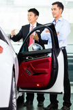 Car Salesman selling auto to customer. Asian Car Salesman selling auto to customer Stock Image