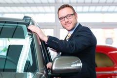 Car Salesman selling auto to customer. Salesman selling car at dealership Stock Image