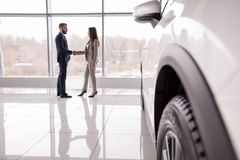 Car Salesman Shaking Hands with Customer. Wide angle portrait of car salesman shaking hands with women buying new car in dealership showroom, car wheel in Royalty Free Stock Image