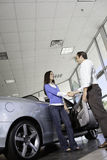 Car salesman shaking hands with female customer in showroom Royalty Free Stock Photo
