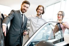 Salesman with couple in the car showroom. Car salesman showing car interior to a young couple clients in the showroom royalty free stock image