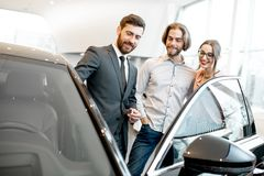 Salesman with couple in the car showroom. Car salesman showing car interior to a young couple clients in the showroom royalty free stock photos