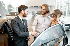 Salesman with couple in the car showroom. Car salesman showing car interior to a young couple clients in the showroom stock images