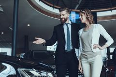 Car Salesman Showing Car to Woman in Showroom. Car Buying Deal. Beautiful Young Woman Talking to Caucasian Handsome Bearded Car Dealership Worker while stock images