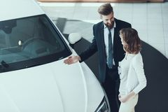 Car Salesman Showing Car to Woman in Showroom. Car Buying Deal. Beautiful Young Woman Talking to Caucasian Handsome Bearded Car Dealership Worker while royalty free stock image