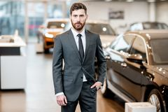 Car salesman in the showroom. Portrait of a handsome salesman in the suit standing at the showroom with luxury cars on the background royalty free stock image