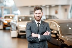 Car salesman in the showroom. Portrait of a handsome salesman in the suit standing at the showroom with luxury cars on the background stock photo