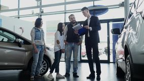 Car salesman shows a young family information about their new car.  royalty free stock photo