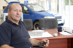 Car salesman sitting in showroom. Looking serious stock image