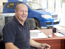 Car salesman sitting in showroom smiling. Looking relaxed royalty free stock photo