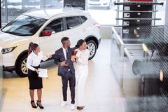 Car salesman standing at dealership telling about features of car to customers royalty free stock photography