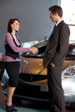 Car salesman standing with female customer by new car in showroom, shaking hands Royalty Free Stock Images