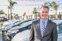 Car salesman. Standing outside a dealership royalty free stock photography