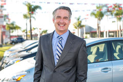 Car salesman. Standing outside a dealership royalty free stock image