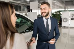 Car Salesman Working with Client. Portrait of handsome car salesman giving keys to young women standing next to white shiny luxury car in dealership showroom Stock Photo