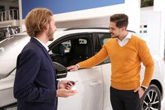 Car salesman working with customer. In dealership royalty free stock photography