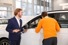 Car salesman working with customer. In dealership royalty free stock images