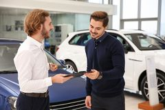 Car salesman working with customer. In dealership royalty free stock photo