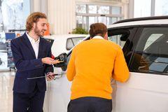 Car salesman working with customer. In dealership stock image