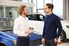 Car salesman working with customer. In dealership stock photography