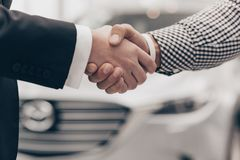 Car salesman working with a customer at the dealership. Cropped close up of a handshake of two men at the dealership salon. Salesman shaking hands with his stock photography