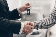 Car salesman working with a customer at the dealership. Cropped close up shot of a men shaking hands with car salesman at the dealership. Car dealer handing stock image