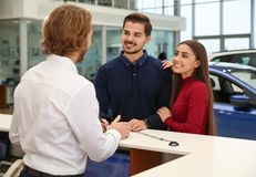 Car salesman and young couple royalty free stock photography
