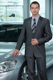 Car salesperson in car showroom Royalty Free Stock Images