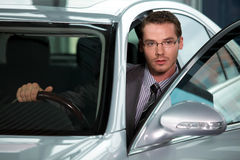 Car salesperson getting in car at showroom Royalty Free Stock Images
