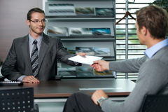 Car salesperson giving catalog to businessman Royalty Free Stock Photos