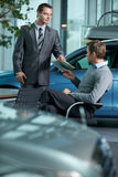 Car salesperson giving catalog to businessman royalty free stock image