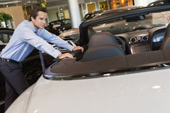 Car salesperson leaning on car Royalty Free Stock Images