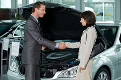 Car salesperson shaking hands with customer at showroom Royalty Free Stock Image