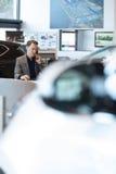 Car salesperson talking on landline phone in car showroom stock photos