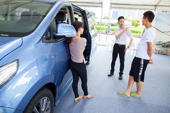 Car salesperson talking with prospective Chinese brand automobile buyer at Dongguan car exhibition in front of large van Stock Photography