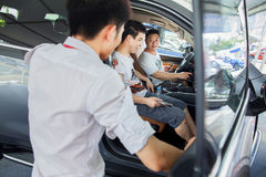 Car salesperson talking with prospective Chinese brand automobile buyers at Dongguan car exhibition Royalty Free Stock Photography