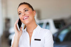 Car saleswoman cell phone. Cheerful car saleswoman talking on cell phone stock images