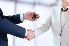 Car saleswoman handing over the keys for a new car to a young business people Stock Photos