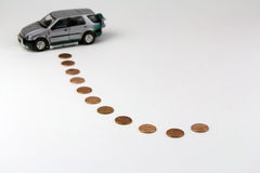 Car saving. A toy car and pennies with white background, a concept of car saving or saving for a car Royalty Free Stock Images