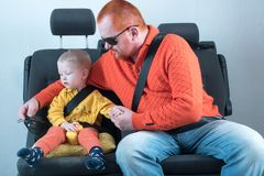 Car seat belt. A happy child is sitting in auto armchair next to man with red hair, beard and mustache in yellow shirt, glasses wi. Th laptop. The concept of Stock Images