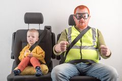 Car seat belt. A happy child is sitting in auto armchair next to man with red hair, beard and mustache in yellow shirt, glasses wi. Car seat belt. A happy child royalty free stock photo