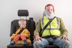 Car seat belt. A happy child is sitting in auto armchair next to man with red hair, beard and mustache in yellow shirt, glasses wi. Car seat belt. A happy child Royalty Free Stock Photography
