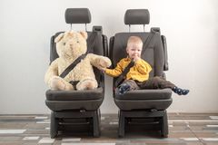 Car seat belt. A happy child is sitting in auto armchair next to a toy bear. The concept of road safety.  Stock Photo
