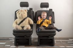 Car seat belt. A happy child is sitting in auto armchair next to a toy bear. The concept of road safety.  Stock Photography