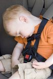 Car seat nap. Young boy is slumped over in built in rental car seat royalty free stock image