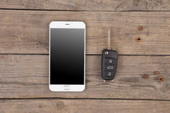 Car security concept - key with remote alarm control and smartphone Stock Images