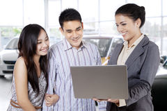 Car seller discussing with couple Royalty Free Stock Photography