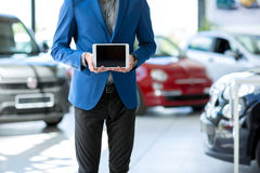 Car seller holding empty pc tablet stock photo
